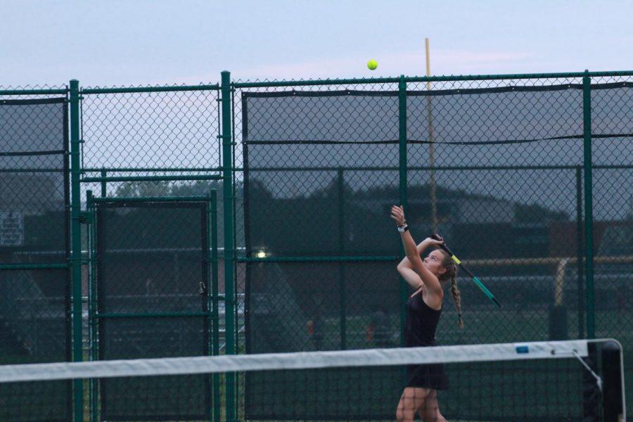Senior Sophia Hennessy serves the ball during  tennis match.